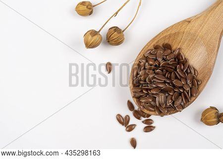 Flax Seeds In A Wooden Spoon. Linen Seed Is Scattered From Spoon On A White Backdrop, With Flax Plan
