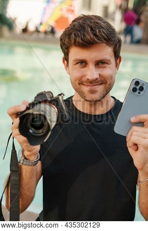 Happy Young Male Photographer Smiling And Showing Contemporary Mobile Phone And Digital Photo Camera