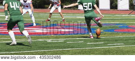 A High School Football Player Is Kicking The Ball During Th Ekickoff Of A Play During A Game.