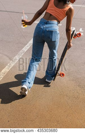 Partial View Of African American Woman Holding Plastic Cup With Orange Juice And Longboard Outside