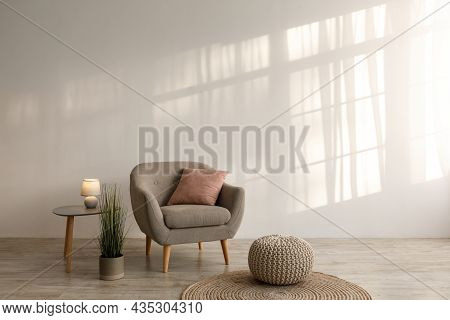 Retro Armchair With Pillow, Luminous Lamp On Table, Potted Plant, Ottoman And Round Carpet On Floor