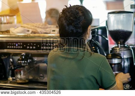 Back View Of Barista Girl Prepares Coffee In Cafe Wearing Surgical Mask Due To The Pandemic Of Coron