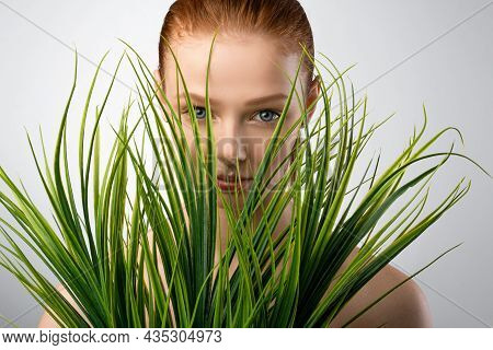Red-haired Girl Posing With Plants On Gray Studio Background