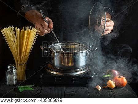 Professional Cook Prepares Italian Pasta In A Saucepan With Vegetables. Close-up Of Cook Hands While