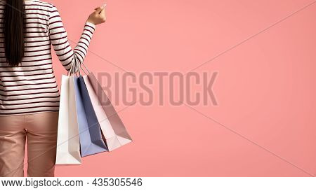 Shopping Concept. Rear View Of Young Female Holding Shopper Bags, Cropped Shot