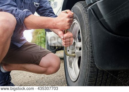 Man Changing Wheel, Hands Unscrewing Bolts On Flat Car Tire On The Road.