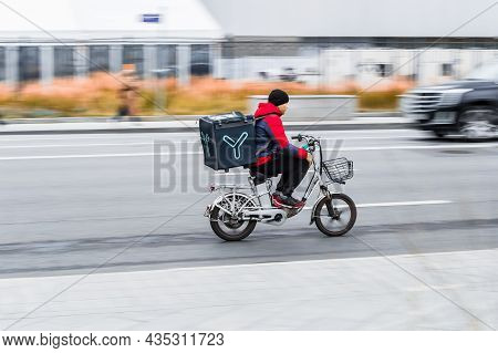 Bicycle Courier Riding On Electric Bike, On His Way To Delivery. Male Courier With Electric Bicycle