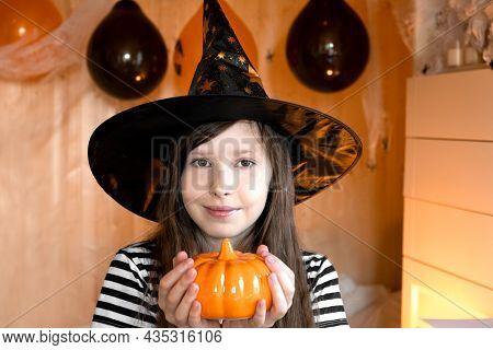 Portrait Of Adorable Teen Girl Wearing Halloween Hat Holding Pumpkin And Smiling. Halloween Home Fam