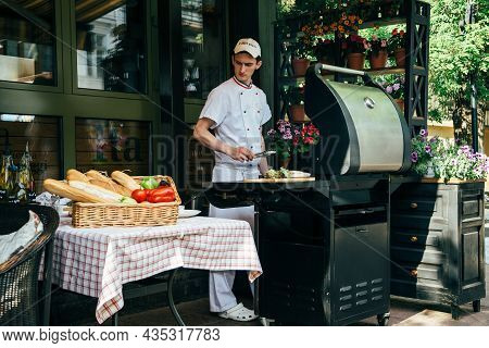 Odessa, Ukraine - May, 11 2014: Cook Working In Italian Outdoor Open Kitchen Pizzeria Restaurant Wit