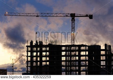Tower Crane And Workers Work At A Construction Site. Silhouette Of A High-rise Building Under Constr
