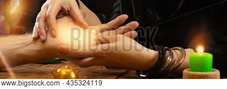 Divination By The Lines Of The Hand. A Fortune Teller Or Oracle Holds A Palm In His Hands, Predictin