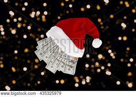 New Year Or Christmas Gift Concept. Money Inside Santa Hat. Christmas Hat Full Of Dollar Bills Isola
