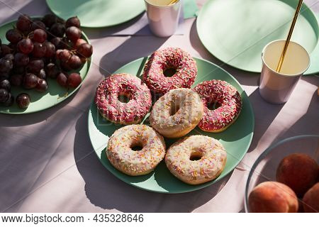 Close Up Of Pink Donuts On Summer Picnic Table Outdoors Decorated For Birthday Party, Copy Space