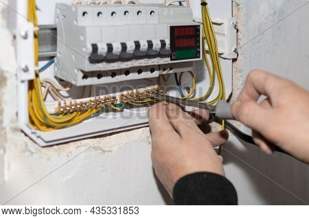 Electrical Switchboard. A Electrician Installs A Multifunctional Shield To Control Electricity Into