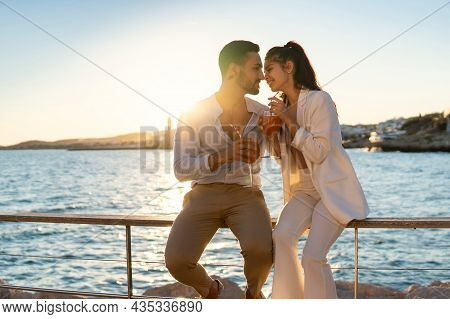 Content Ethnic Couple In Love Sitting Close To Each Other On Embankment Against Sea And Drinking Coc
