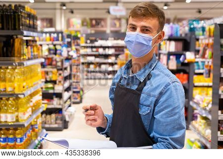 Young Man Working In A Grocery Store Wearing Protective Medical Mask For Protection From Virus Over