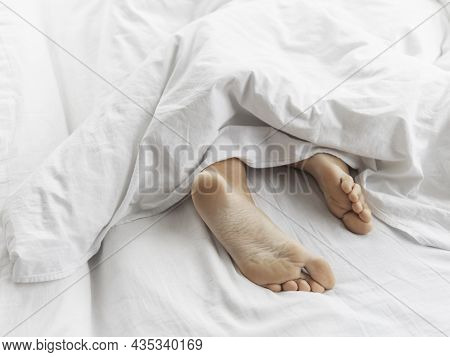 View On Bare Feet Under Blanket. Bedroom Lit With Morning Light. Woman Sleeps With Comfort. White Cr