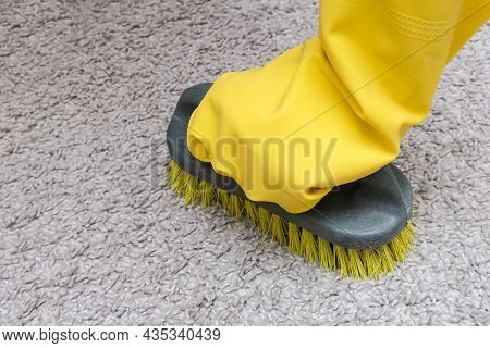 A Hand In Yellow Protective Rubber Glove Cleaning Carpet With A Brush Close Up, Housekeeping And Tid