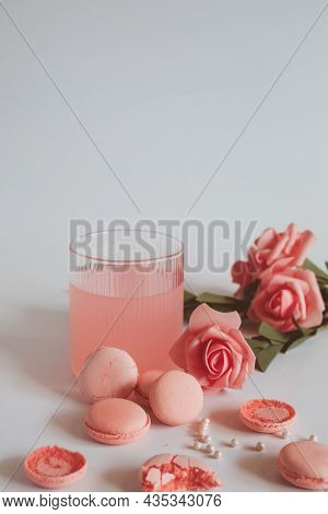 Pink Macaron Cookies And Rose Flowers On White Background. French Cookie. Soft Pastel Vintage Tone.