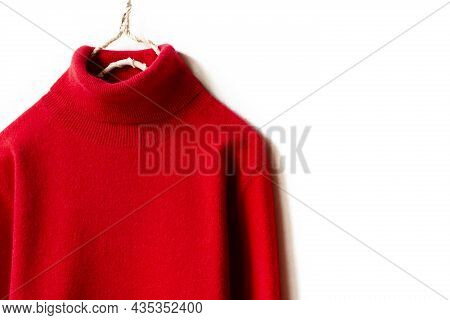 Red Wool Sweater Hanging On Clothes Hanger On White Background.close Up.