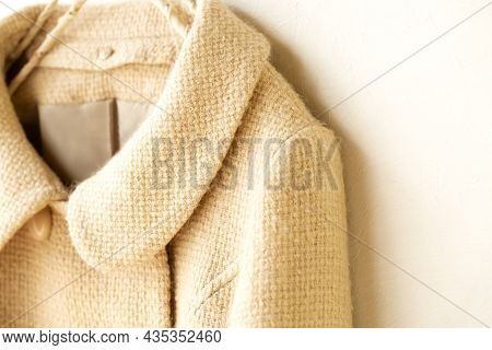 Beige Wool Coat Hanging On Clothes Hanger On White Background.close Up.
