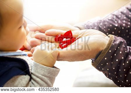 An Adult Puts A Lot Of Motifs Of The Hearts On The Hand. The Baby Looks Into That Hearts On White Ba