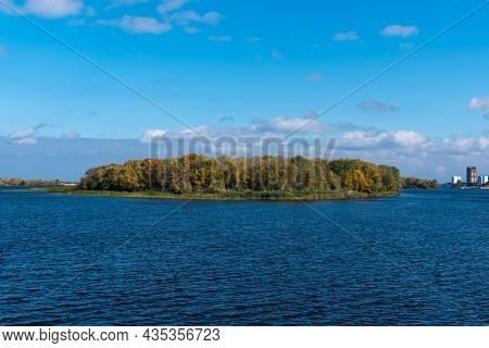 Autumn River Landscape On A Sunny Day - An Island On The River Overgrown With Forest With Leaves Beg