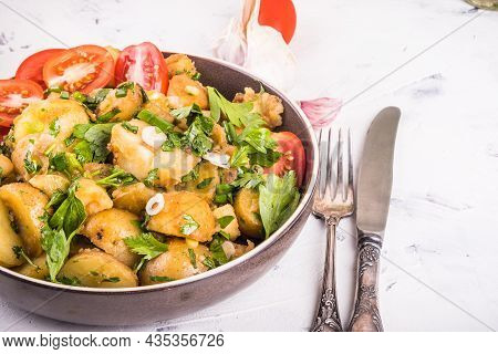 Portion Of Potato Salad With Herbs And Tomatoes In A Plate Close-up