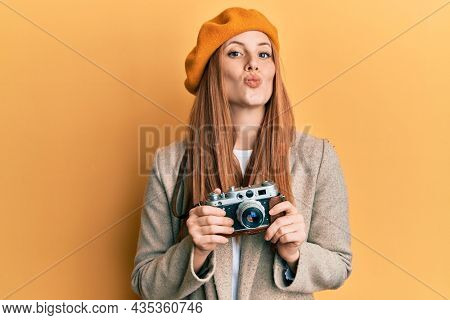 Young irish woman holding vintage camera looking at the camera blowing a kiss being lovely and sexy. love expression.