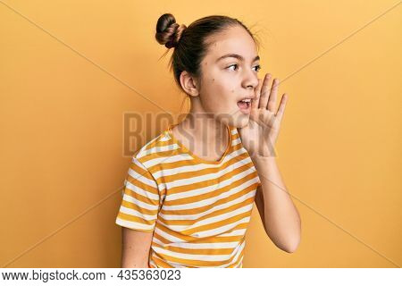 Beautiful brunette little girl wearing casual striped t shirt hand on mouth telling secret rumor, whispering malicious talk conversation