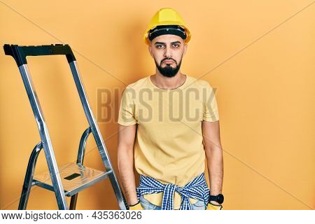 Handsome man with beard by construction stairs wearing hardhat depressed and worry for distress, crying angry and afraid. sad expression.