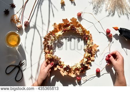 Hands Making Dried Floral Wreath From Dry Autumn Leaves And Fall Berries. Hands In Sweater With Mani