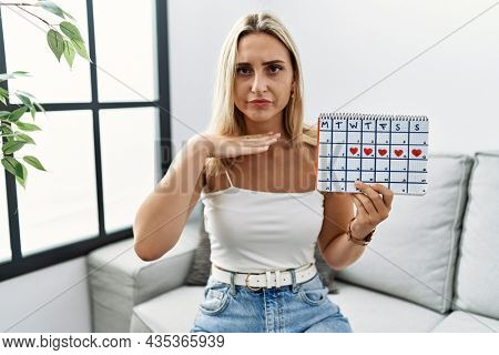 Young blonde woman holding heart calendar cutting throat with hand as knife, threaten aggression with furious violence