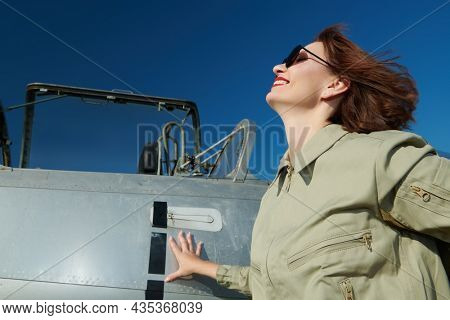Portrait of a beautiful woman pilot wearing uniform and sunglasses posing by her fighter-jet cheerfully laughing. Blue sky background. Military aircraft.