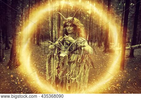 Female shaman in an ethnic dress and deer antlers headdress creating a magic portal with a help of a ritual staff. Fantasy concept, magic. Paganism. Halloween.