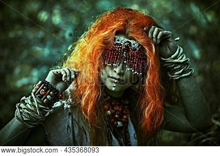 Frightening forest witch with a mask covering her eyes standing in a dark gloomy forest. Woman shaman. Paganism. Death ritual. Halloween.