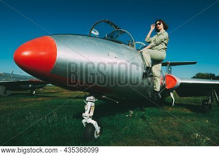Beautiful pilot woman in a uniform and sunglasses getting on her fighter jet to start the flight. Military and commercial aircraft. Full length portrait in the background of an airfield and a blue sky