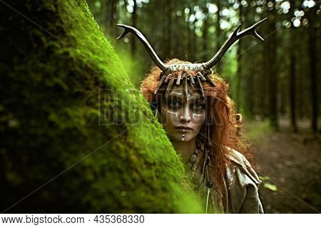 A mystical woman shaman in an ethnic dress and deer antlers headdress peeping out from behind a tree in the forest. Fairy forest witch. Fantasy. Halloween.