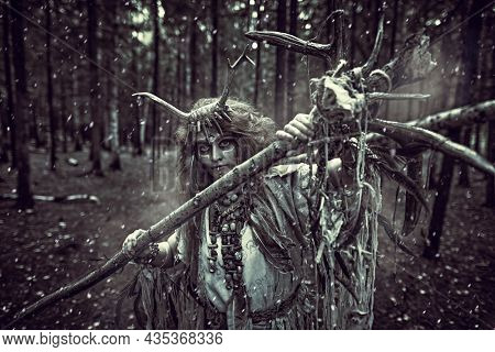 Female shaman in an ethnic dress and deer antlers headdress creating a snowstorm in a gloomy dense forest with her ritual staff . Fantasy concept, magic. Paganism. Halloween.