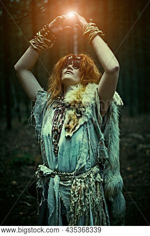Portrait of a scary forest witch with a mask on her eyes making a ball of energy with a help of her mystical forces. Woman shaman. Paganism. Halloween.