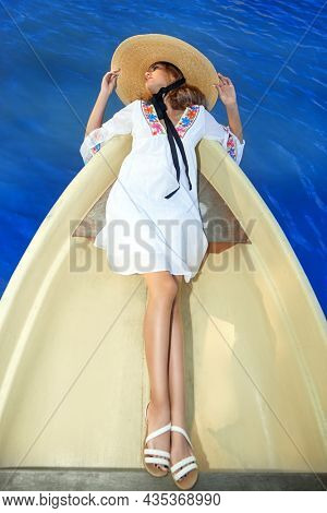 Summer vacation. Beautiful tanned blonde girl in a light white dress and a wide-brimmed straw hat enjoying a sea trip in a boat. Summer fashion and beauty.