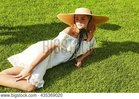Gorgeous elegant blonde girl in a  white dress and wide-brimmed straw hat lying on a green lawn on a lovely sunny day. Summer vacation. Summer beauty, fashion.
