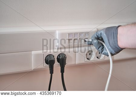 Connection To A Computer Network In The Office, A Gloved Hand Holds A Cord For Connecting To An Inte