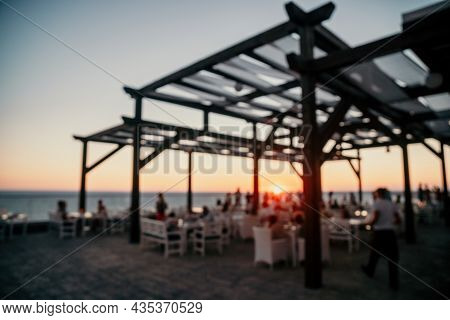 Abstract Blurred Image Of Outdoor Restaurant Terrace On Warm Summer Evening Sunset Over The Sea With