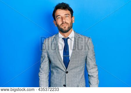 Handsome man with beard wearing business suit and tie relaxed with serious expression on face. simple and natural looking at the camera.