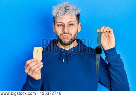 Young hispanic man with modern dyed hair holding wireless earphones and smart watch puffing cheeks with funny face. mouth inflated with air, catching air.