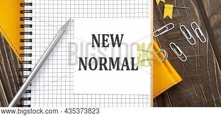 New Normal Text On Sticker On The Notebook, Wooden Background