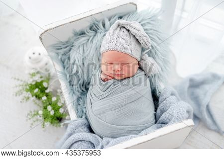 Portrait of newborn baby boy swaddled in light blue fabric and wearing knitted hat sweet sleeping on white small designed bed. Adorable infant child napping during studio photoshoot