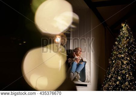 Young Happy Girl Relaxing On The Windowsill Near The Christmas Tree.
