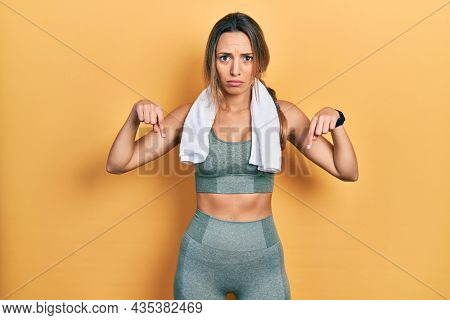 Beautiful hispanic woman wearing sportswear and towel pointing down looking sad and upset, indicating direction with fingers, unhappy and depressed.